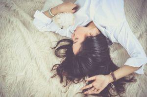 白い絨毯の上に横たわるお肌がツルツルの女性